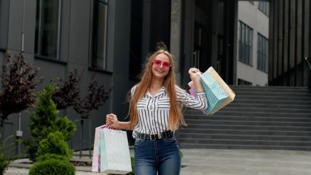 vídeos de stock, filmes e b-roll de garota levantando sacolas de compras, olhando satisfeito com a compra, desfrutando de descontos na black friday - arméria