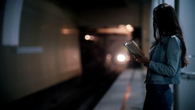 girl reading a book on the edge of the platform, slow motion - сбежавший из дома стоковые видео и кадры b-roll