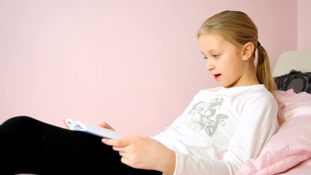 Girl reading book on bed Little girl reading book on bed with pillows in her bedroom wisdom stock videos & royalty-free footage