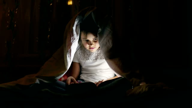 girl reading book with a flashlight under the covers at night video