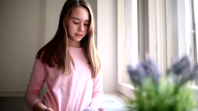 Girl reading magazine at home video