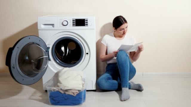 mädchen liest anweisung für waschmaschine in der nähe von beige wand - waschmaschine wand stock-videos und b-roll-filmmaterial