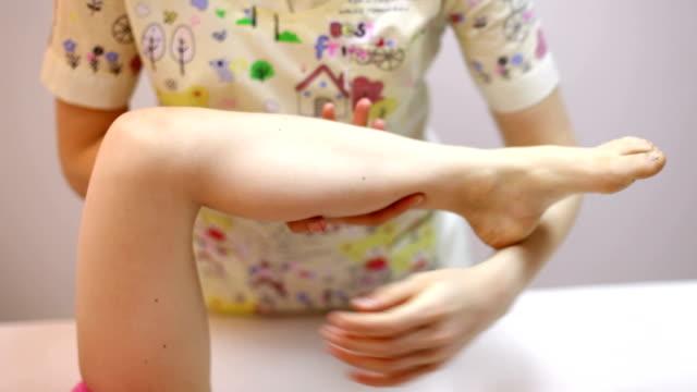 vídeos y material grabado en eventos de stock de chica recibiendo tratamiento osteopático de la pierna - quiropráctico