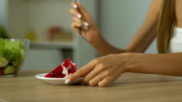 Jeune fille refuse de manger de salade, choisit le gâteau, manque de maîtrise de soi, tentation, closeup - Vidéo