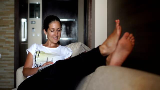 stockvideo's en b-roll-footage met meisje ontspannen thuis - woman home magazine
