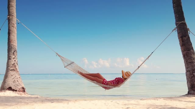 Girl relaxing in a hammock on tropical island beach. Summer vacation in Punta Cana, Dominican Republic