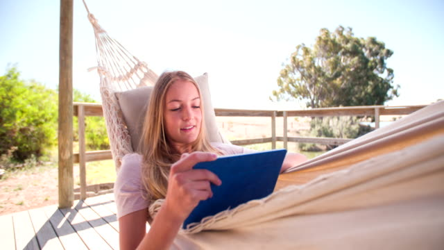 Girl relaxing in a hammock using a digital tablet Teen girl using a digital tablet while relaxing in a hammock near a lake, Panning in Slow Motion lying down stock videos & royalty-free footage