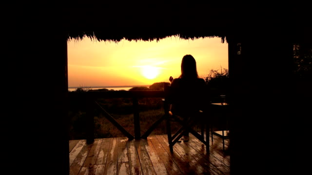 CLOSE UP: Girl relaxing on veranda watching stunning bushland and golden sunrise CLOSE UP: Young girl in luxury glamping Lake Burunge Tented Camp sitting on raised wooden porch, relaxing stretching legs on fence and admiring bushy landscape and beautiful golden light sunrise tanzania stock videos & royalty-free footage
