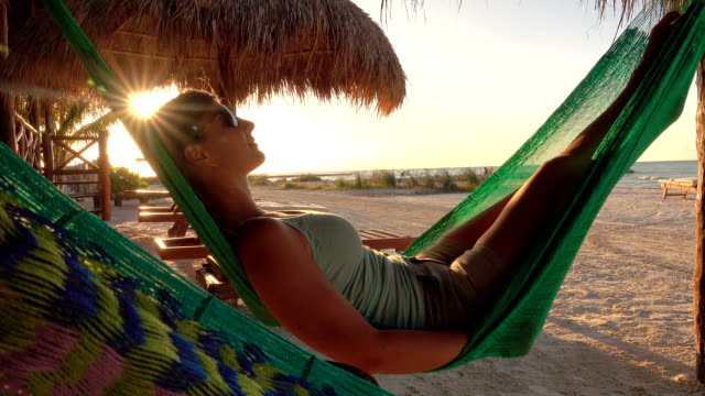 close up: girl relaxing, swinging in hammock overlooking sandy beach at sunset - amaca video stock e b–roll