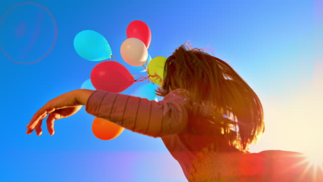 slo mo girl releasing a bunch of colourful balloons into the sky - vivid 4k video stock videos & royalty-free footage