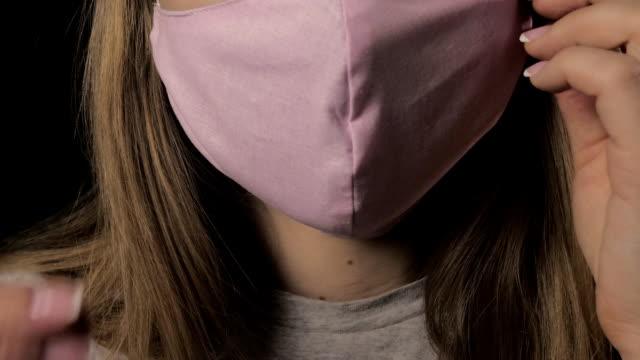 mädchen entfernt eine rosa maske und beginnt zu husten. isoliert auf schwarzem hintergrund. gesundheitsversorgung und medizinisches konzept. nahaufnahme porträt . fullhd. coronavirus-epidemie - entfernt stock-videos und b-roll-filmmaterial