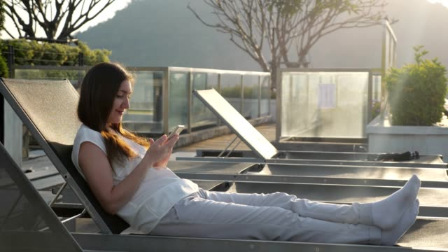 girl rests in chair texting on phone at hotel against hill
