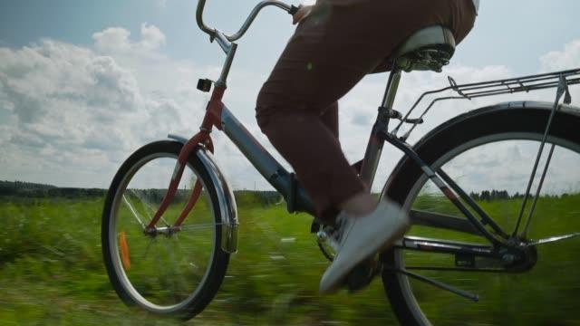 flickan rider en röd cykel genom ett grönt fält - ben bildbanksvideor och videomaterial från bakom kulisserna
