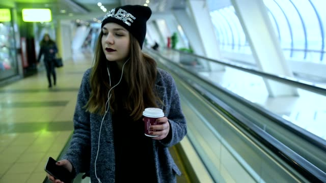 girl rides on travelators and drink coffee - tasty movie filmów i materiałów b-roll