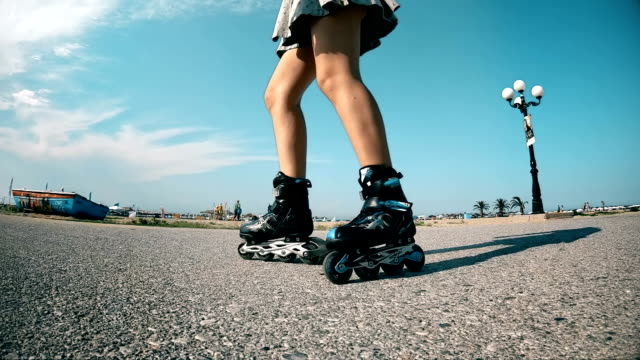 girl rides roller blades along the pavement on the waterfront in the morning at dawn. healthy lifestyle, slow motion - łyżwa filmów i materiałów b-roll