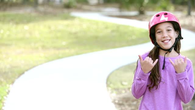 Girl rides skateboard in park toward the camera video