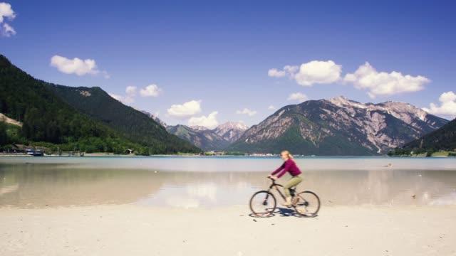 美しい高山に対する砂浜のビーチで自転車に乗る女の子。 - チロル州点の映像素材/bロール