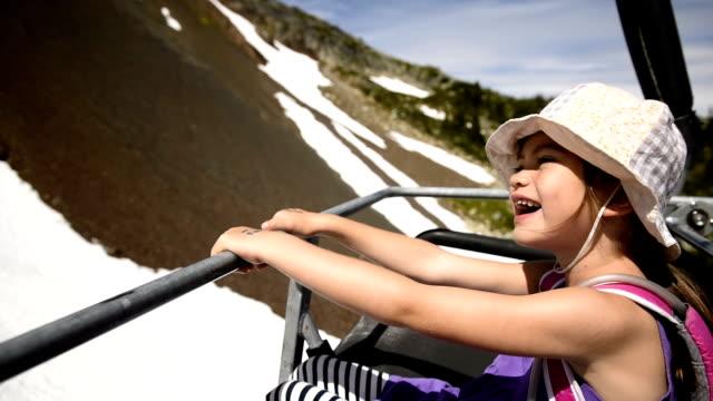 vídeos de stock e filmes b-roll de girl riding a chairlift in summer - montanha costeira