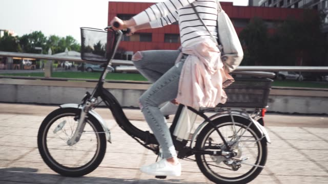 Girl riding e-bike Girl riding e-bike in the city atmosphere cycle vehicle stock videos & royalty-free footage