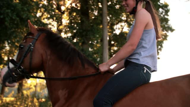 Girl riding her horse down a sunlit park lane video