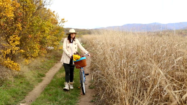 girl riding on bike through autumnal forest - cestino della bicicletta video stock e b–roll