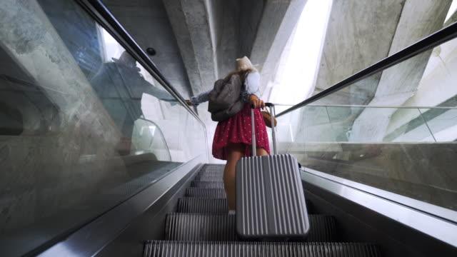 girl riding on escalator in modern terminal - donna valigia solitudine video stock e b–roll