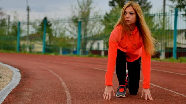 flicka-löpare som förbereder sig för att starta - tävlingsdistans bildbanksvideor och videomaterial från bakom kulisserna