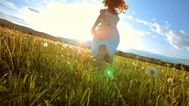 super slow-motion ragazza in esecuzione sul prato al tramonto - children video stock e b–roll