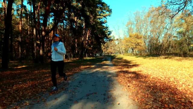 flicka kör i skogen morgon. idrott - tävlingsdistans bildbanksvideor och videomaterial från bakom kulisserna