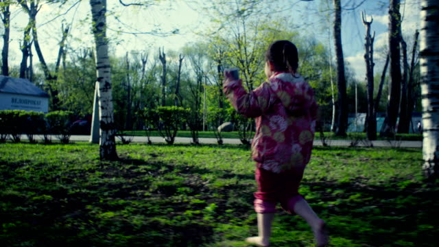 a girl running in the park - giovane nell'animo video stock e b–roll