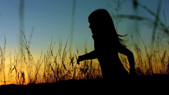 LA TS SLO MO Girl Running In The Sunset HD1080p: MEDIUM LOW ANGLE TRACKING SLOW MOTION shot of a silhouette of a little girl running in the grass at the sunset. Profile view. one girl only stock videos & royalty-free footage