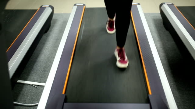 Girl running on a treadmill in the fitness room