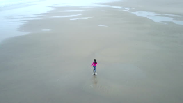 Girl running on the huge beach video