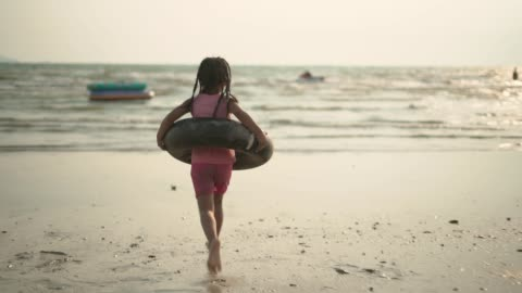 A girl running toward the sea with a flotation tube A young girl running toward the sea with a black flotation tube at beach following moving activity stock videos & royalty-free footage