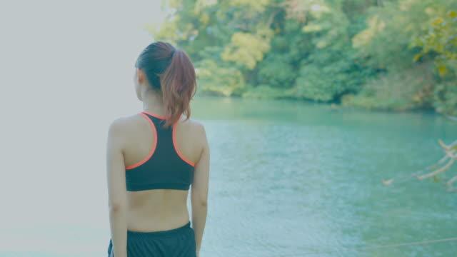 Girl running wih headphones in the park video