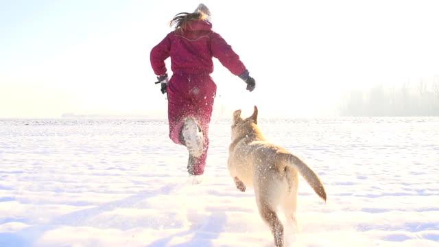 slo mo girl running with a puppy in snow - snow kids bildbanksvideor och videomaterial från bakom kulisserna