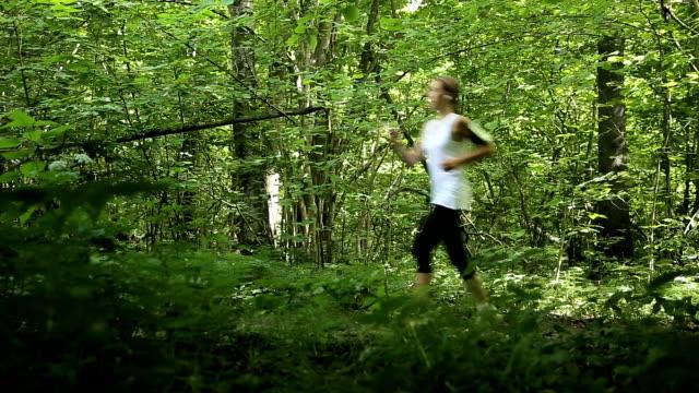 tjejen kör på vägen i ett fält - tävlingsdistans bildbanksvideor och videomaterial från bakom kulisserna