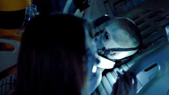 stockvideo's en b-roll-footage met meisje wetenschapper bewaakt de toestand van een vreemdeling in een operatie. ruimtelaboratorium, operationele eenheid. - ventilator bed