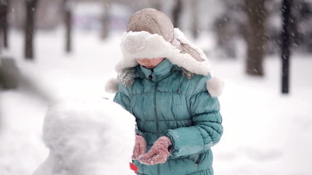 Girl sculpts a snowman in the snow in winter. video