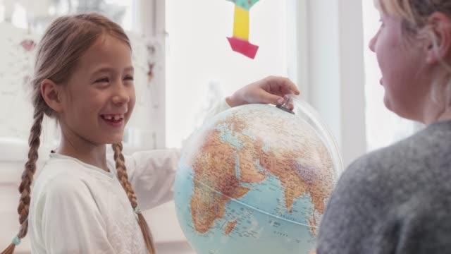 flicka som söker efter en plats på globen i klass rummet - bordsjordglob bildbanksvideor och videomaterial från bakom kulisserna