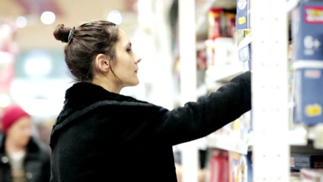 Girl selects the item on the shelves in the store video