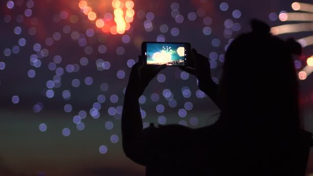A girl shoots fireworks on a smartphone. slow motion