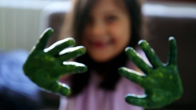 ragazza che mostra le mani coperte di vernice verde - arti e mestieri video stock e b–roll