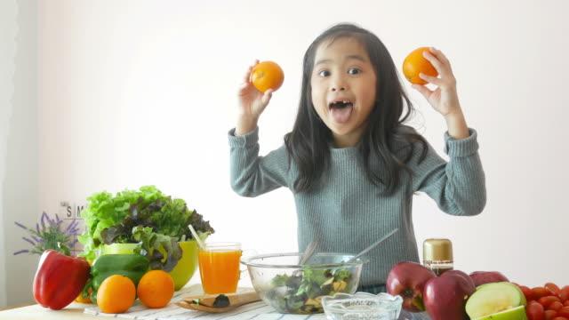tjej visar hur man matlagning sallad, spelar peekaboo spel - apelsin bildbanksvideor och videomaterial från bakom kulisserna