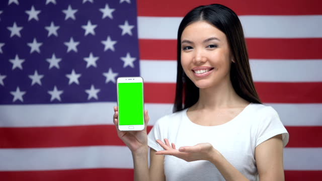 Girl showing smartphone with green screen, US flag on background, translator app