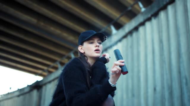 vídeos de stock e filmes b-roll de girl showing smoke grenade at camera. woman holding smoke bomb in hand - focagem