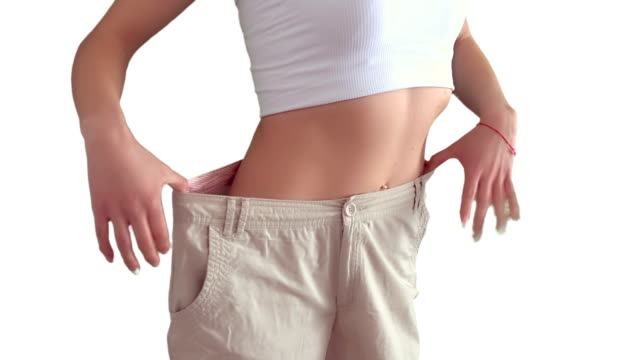 girl shows that she has lost weight - chudy filmów i materiałów b-roll
