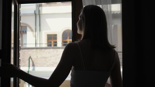 stockvideo's en b-roll-footage met meisje silhouet opent venster tegen buurman huis - buren