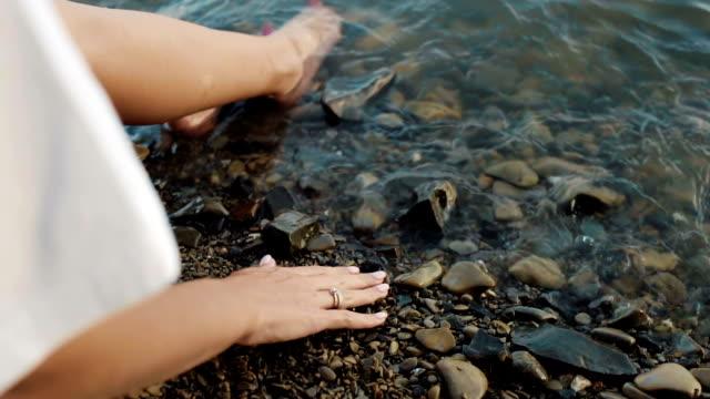 Girl sit on beach and toutch rocks video