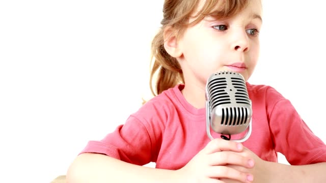 Girl sits at table and sings in microphone video